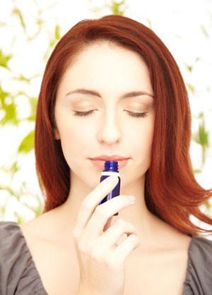 woman smelling essential oils bottle