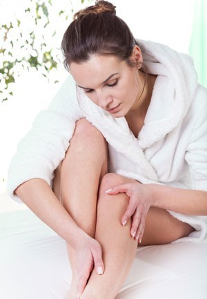 woman applying essential oils to bottom of legs