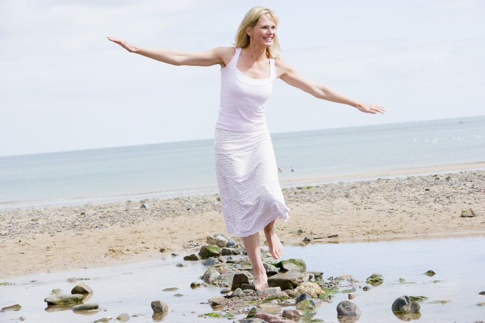happy woman walking along beach balancing on rocks